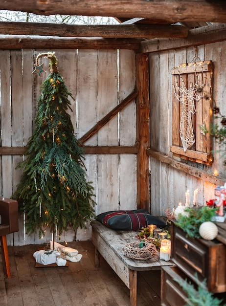 Natale e rifiuti zero, albero di natale fatto di abete e rami con le tue mani, fatto a mano. interior design in stile rustico sulla terrazza di capodanno. h Foto Premium