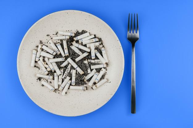 La sigaretta si intromette un piatto e una forcella su uno spazio blu della copia del fondo. sigarette per il pranzo. Foto Premium