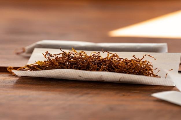 Carta per sigarette e mucchio di tabacco sul tavolo di legno Foto Premium
