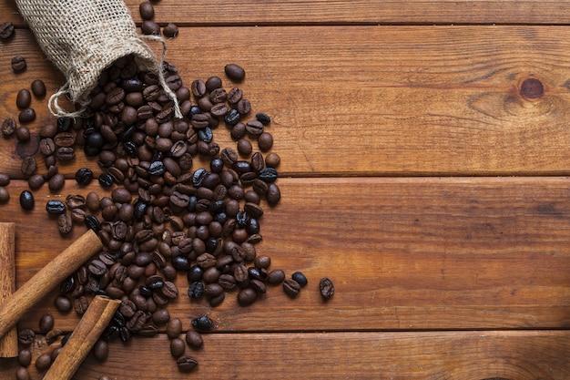 Cannella vicino a chicchi di caffè versato Foto Premium