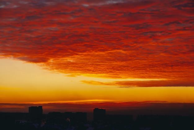 Paesaggio urbano con l'alba infuocata del vampiro di sangue. incredibile caldo cielo nuvoloso drammatico sopra sagome scure di edifici della città. luce solare arancione. sfondo atmosferico di alba in tempo nuvoloso. copia spazio. Foto Premium