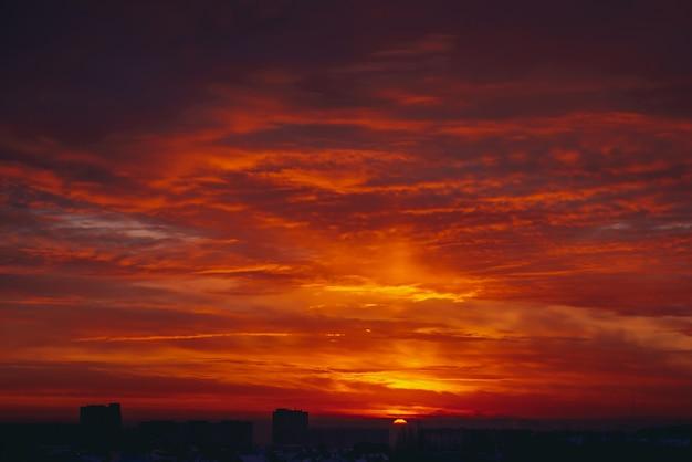 Paesaggio urbano con vivida alba infuocata. incredibile caldo cielo nuvoloso drammatico sopra sagome scure di edifici della città. luce solare arancione. sfondo atmosferico dell'alba in tempo nuvoloso. copyspace. Foto Premium