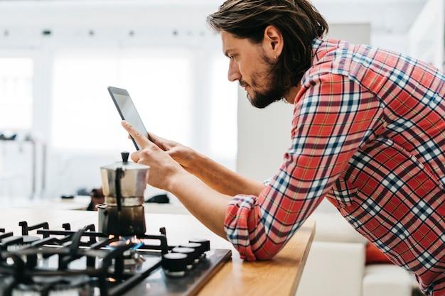 Macchinetta del caffè classica su fuoco di gas con un uomo che esamina compressa digitale nella cucina Foto Premium
