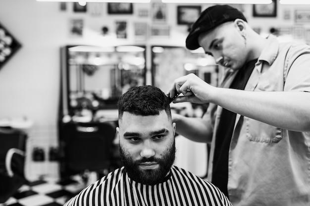 Taglio di capelli classico in un barbiere. curva lo styling dei capelli e l'assistenza sanitaria dei capelli in un negozio di barbiere. taglio di capelli da uomo. Foto Premium