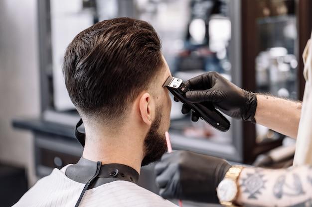 Taglio di capelli classico in un barbiere. curva lo styling dei capelli e l'assistenza sanitaria dei capelli in un negozio di barbiere. uomini Foto Premium