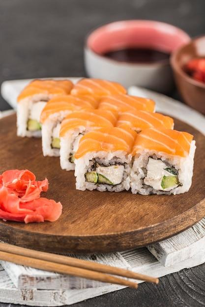 Rotoli di sushi classici philadelphia su una tavola di legno con zenzero, salsa di soia e bacchette su una superficie scura Foto Premium