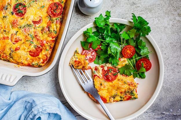 Classica frittata al forno o frittata con pomodori, peperoni e formaggio in piatto bianco, sfondo grigio chiaro. Foto Premium