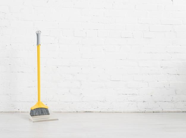 Scopa di pulizia con muro di mattoni bianchi Foto Premium