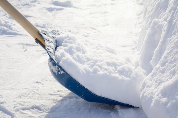 Pulizia della neve con una pala in campagna dopo una forte nevicata Foto Premium