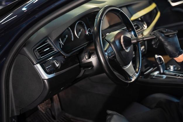 Pulizia del volante dell'auto dallo sporco con la spazzola Foto Premium