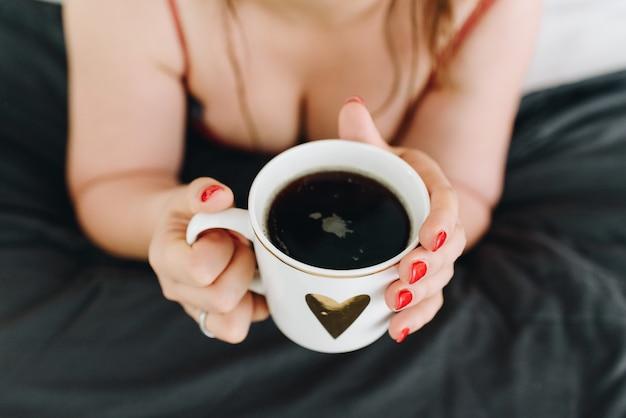 Scollatura o seno femminile, giovane donna che beve una tazza di caffè Foto Premium