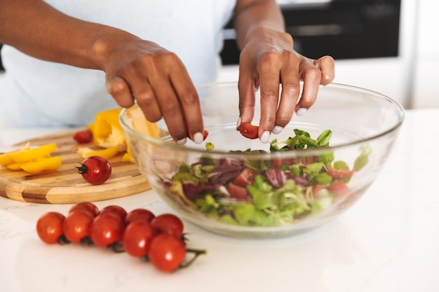 Primo piano di una donna afro-americana che produce un'insalata Foto Premium