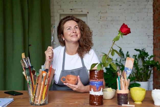 Primo piano sulla donna artigiana che lavora con un pennello Foto Premium