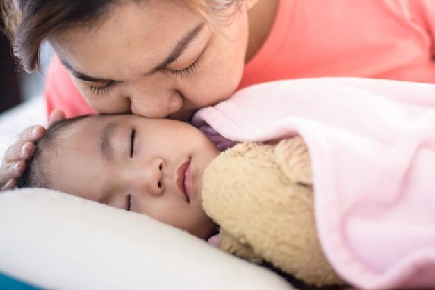 Chiuda sulla madre asiatica che bacia la sua neonata che dorme sul letto. Foto Premium