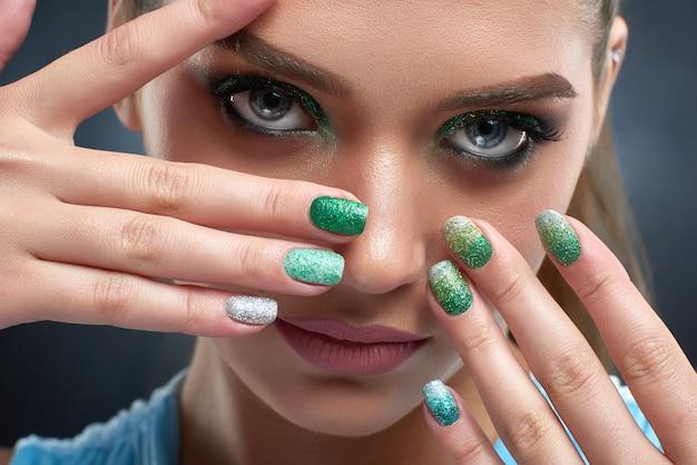 Chiuda in su di bella donna castana con manicure lucida, trucco nei colori verdi, pelle color bronzo. attraente ragazza in posa, nascondendo il viso, mostrando le unghie. concetto di bellezza. Foto Premium