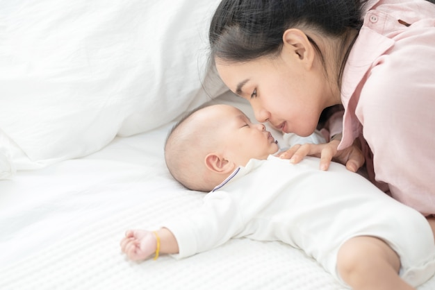 Chiuda sulla bella giovane madre asiatica che bacia il neonato sul letto. sanità e medicina. ragazza asiatica amore stile di vita. Foto Premium