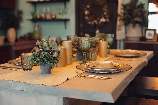 Primo piano del tavolo da pranzo splendidamente decorato con abeti in vasi e candele d'oro. servizi di piatti per quattro persone. Foto Premium