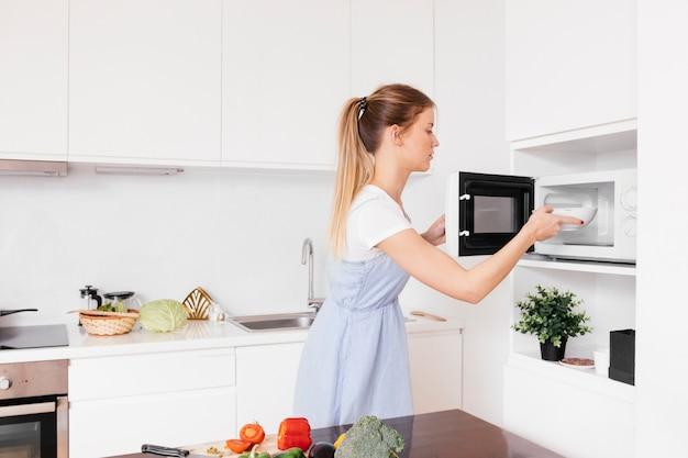 Primo piano della giovane donna bionda che inserisce alimento nel forno a microonde Foto Premium