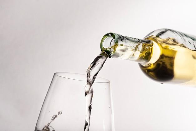 Bottiglia di close-up versando il vino nel bicchiere Foto Premium