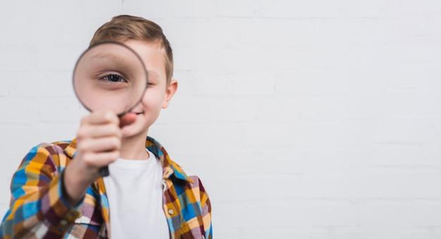 Primo piano di un ragazzo che osserva tramite la lente d'ingrandimento contro fondo bianco Foto Premium