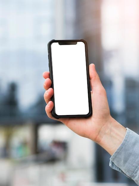 Primo piano del telefono cellulare della tenuta della mano dell'uomo d'affari con la visualizzazione di schermo bianca Foto Premium