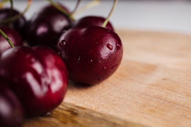 Primo piano di un frutto ciliegia su una tavola di legno Foto Premium
