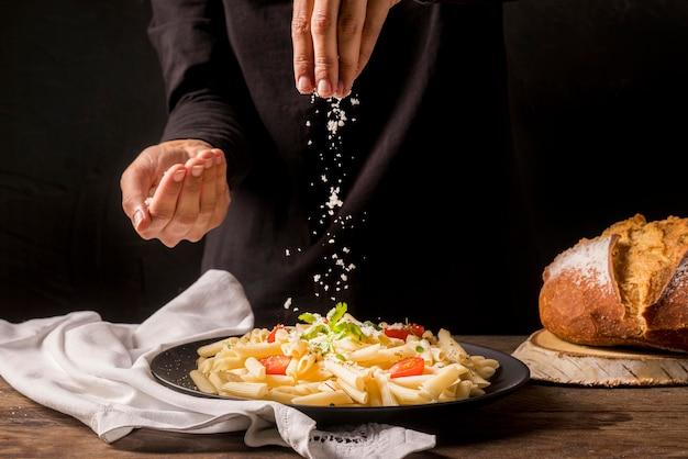 Formaggio di versamento del cuoco del primo piano su pasta Foto Premium