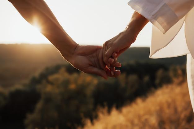 Primo piano di coppia mano nella mano sulla collina. primo piano delle mani. Foto Premium