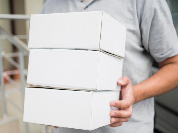 Corriere del primo piano che tengono le scatole Foto Premium