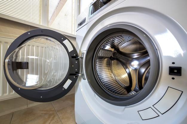 Dettaglio del primo piano dell'interno moderno della lavatrice con l'interno della porta aperta. tamburo inossidabile lucido argento, design e tecnologia. Foto Premium