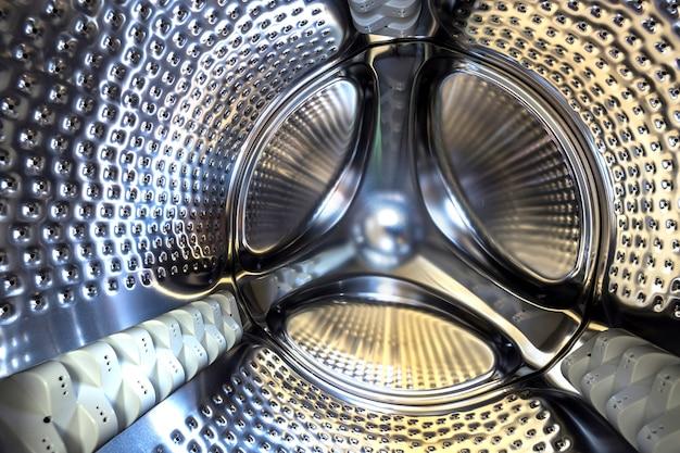 Dettaglio del primo piano, tamburo inossidabile dell'interno moderno della lavatrice. progettazione di superficie lucida d'argento astratta. Foto Premium