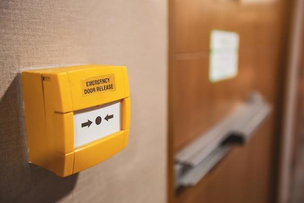 Primo piano, l'interruttore di rilascio della porta di emergenza si trova sulla porta di uscita antincendio Foto Premium