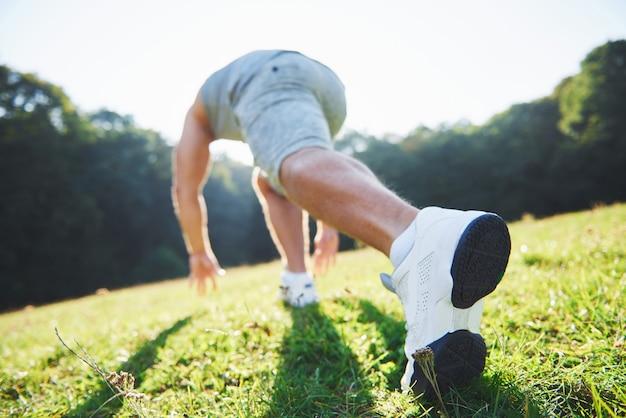 Primo piano dei piedi di un uomo che corre nell'erba. Foto Premium