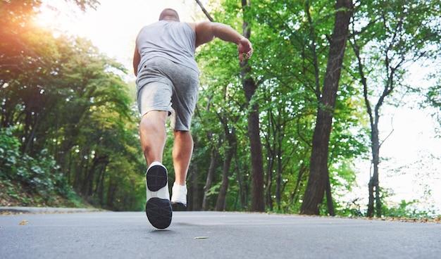 Chiuda in su dei piedi dell'uomo giovane corridore che corre lungo la strada nel parco. Foto Premium