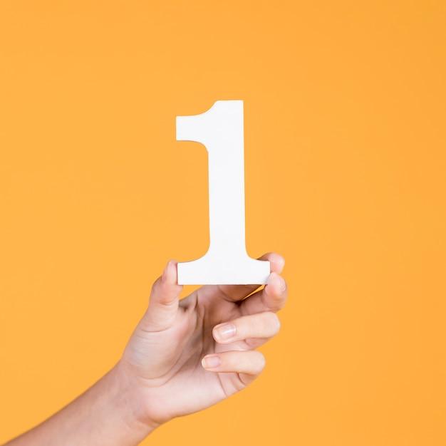 Primo piano del ritaglio femminile della carta di numero uno della tenuta della mano Foto Premium