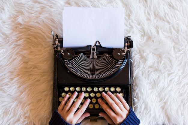 Chiuda su delle mani femminili che scrivono sulla retro macchina da scrivere. la tazza di caffè è sul lato destro. vista dall'alto. Foto Premium