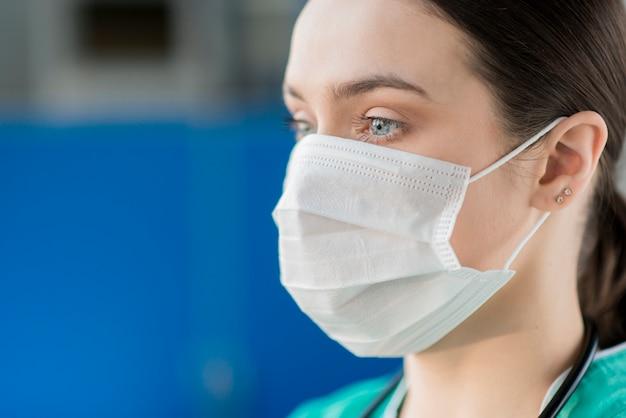 Maschera d'uso dell'infermiera femminile del primo piano Foto Premium