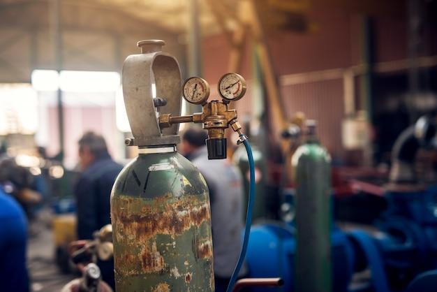 Primo piano vista di messa a fuoco di apparecchiature di saldatura. bombola di gas acetilene serbatoio con manometro regolatori manometri nell'officina tessuto industriale. Foto Premium