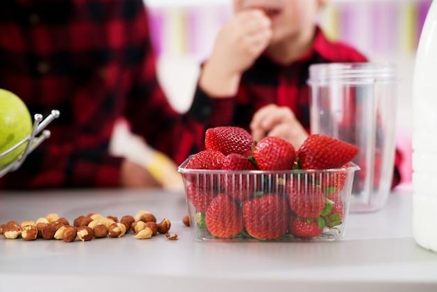 Chiuda in su delle fragole fresche e sane in ciotola di plastica e nocciole su un contatore in una cucina molto luminosa. Foto Premium