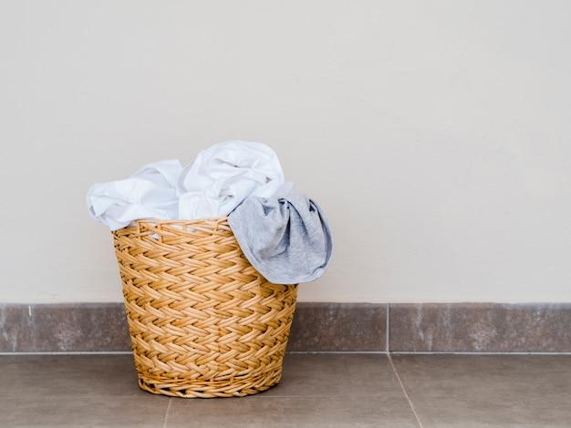 Chiuda sul cestino di lavanderia pieno del ramoscello Foto Premium