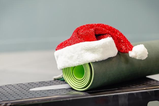 Primo piano di stuoia grigia con cappello di babbo natale in palestra. miglior regalo di natale per persona attiva. concetto di natale di yoga. Foto Premium