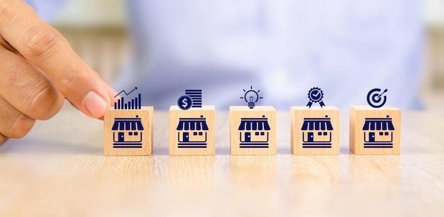 La mano del primo piano sceglie i blocchi di legno del giocattolo del cubo disposti in linea con l'icona del negozio di affari di franchising. Foto Premium