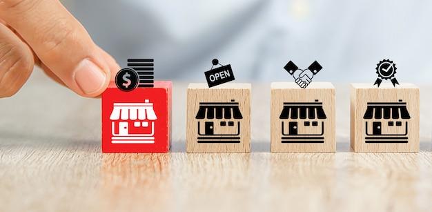 La mano del primo piano sceglie il posto dei blocchi di legno del giocattolo del cubo in linea con l'icona del negozio di affari di franchising. Foto Premium