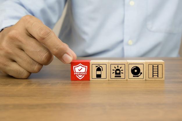 La mano del primo piano sceglie l'icona di prevenzione sui blocchi di legno del giocattolo del cubo accatastati con l'icona di prevenzione dell'uscita di fuoco. Foto Premium
