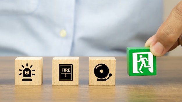La mano del primo piano sceglie un blocco di legno del giocattolo impilato con l'icona dell'uscita del fuoco Foto Premium