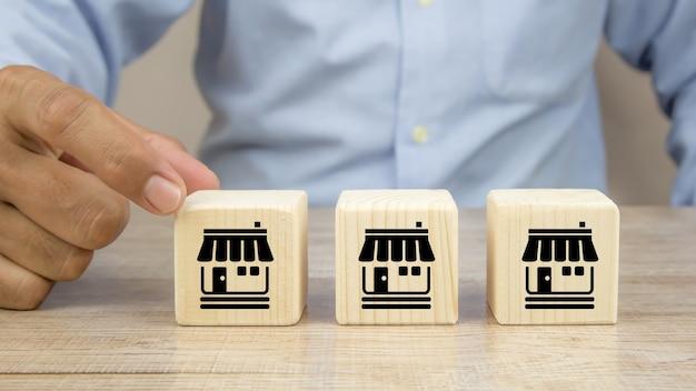 La mano del primo piano sceglie i blocchi di legno del giocattolo del cubo impilati con l'icona del negozio di affari di franchising. Foto Premium