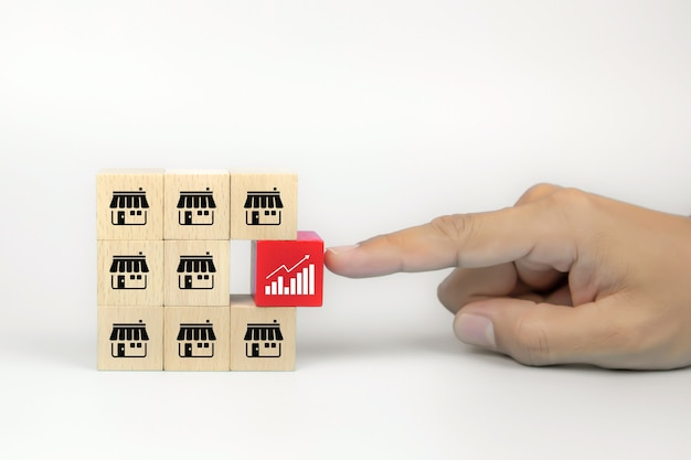 La mano del primo piano sceglie l'icona del grafico sui blocchi di legno del giocattolo del cubo impilati con l'icona del negozio di affari di franchising. Foto Premium
