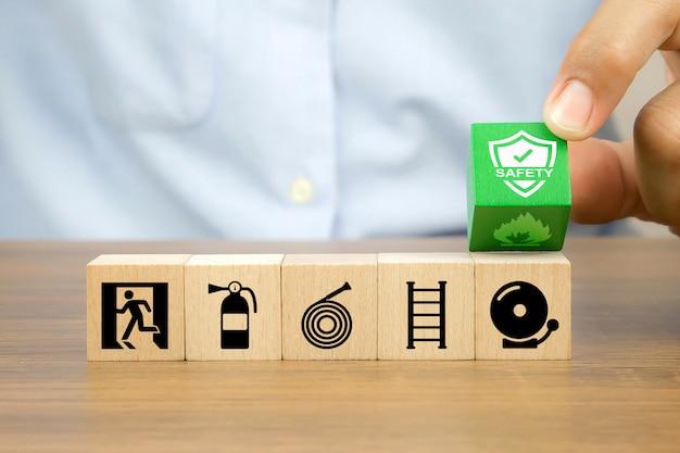 La mano del primo piano sceglie impedisce il simbolo sui blocchi di cubo di legno impilati con l'icona dell'uscita di sicurezza Foto Premium