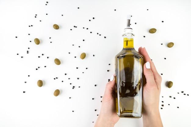 Bottiglia della tenuta della mano del primo piano di olio d'oliva Foto Premium