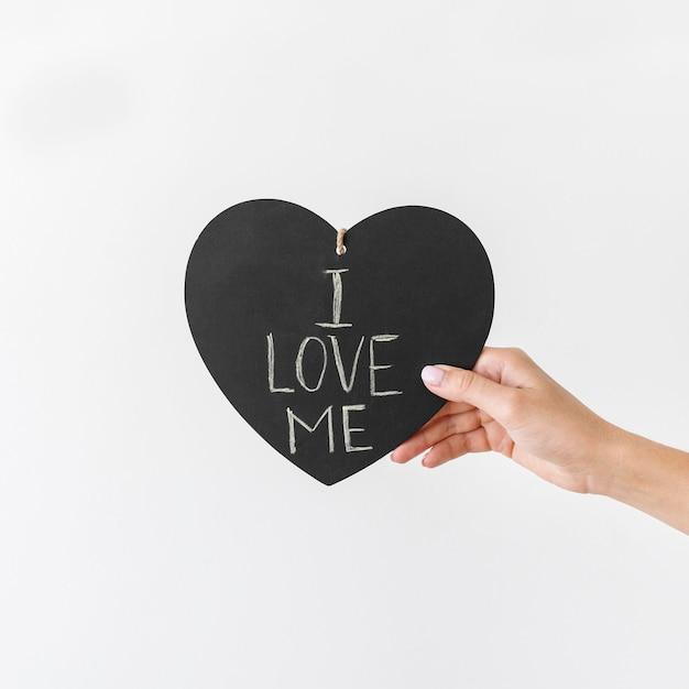 Primo piano mano che tiene il cuore con il testo Foto Premium